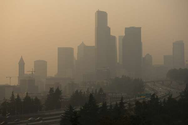 SEATTLE, WA - SEPTEMBER 11: Cars drive on I-5 in front of a hazy Seattle skyline due to wildfire smoke on September 11, 2020 in Seattle, Washington. According to reports, air quality is expected to worsen as smoke from dozens of wildfires in forests of the Pacific Northwest and along the West Coast descends onto the region. (Photo by Lindsey Wasson/Getty Images)