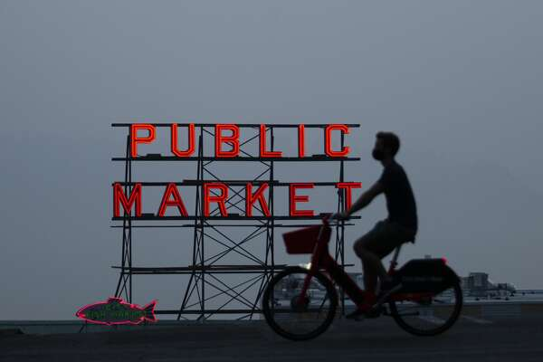 SEATTLE, WA - SEPTEMBER 11: Wildfire smoke obscures the view of Elliott Bay as a person bikes past a Pike Place Market sign on September 11, 2020 in Seattle, Washington. According to reports, air quality is expected to worsen as smoke from dozens of wildfires in forests of the Pacific Northwest and along the West Coast descends onto the region. (Photo by Lindsey Wasson/Getty Images)
