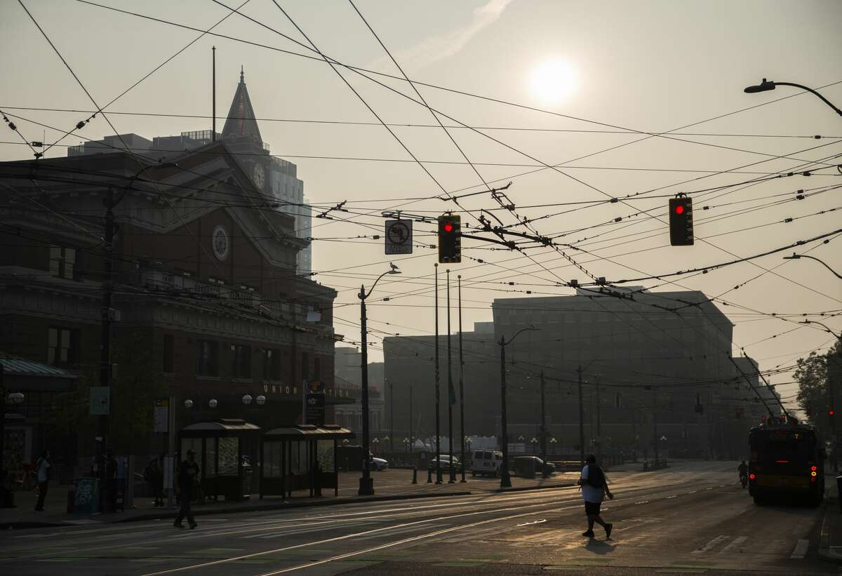 Pedestrians cross the street under a hazy sky due to wildfire smoke in the Chinatown-International District on September 11, 2020 in Seattle, Washington.