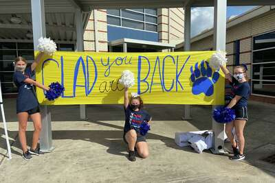 Cheer students pose next to a sign welcoming students back to Bear Branch Junior High School in Magnolia ISD, which began on-campus instruction Sept. 8, 2020.
