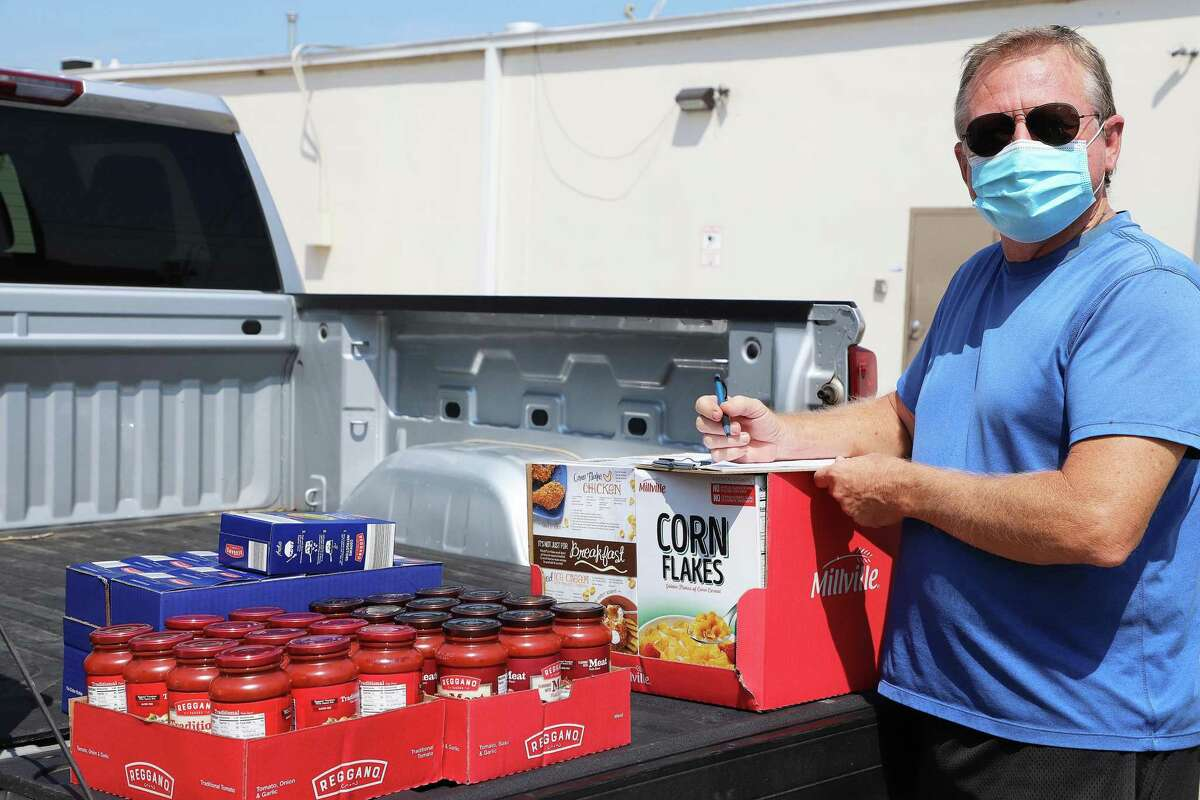 Clients and volunteers are masked up as they pickup or load up food for the needy.