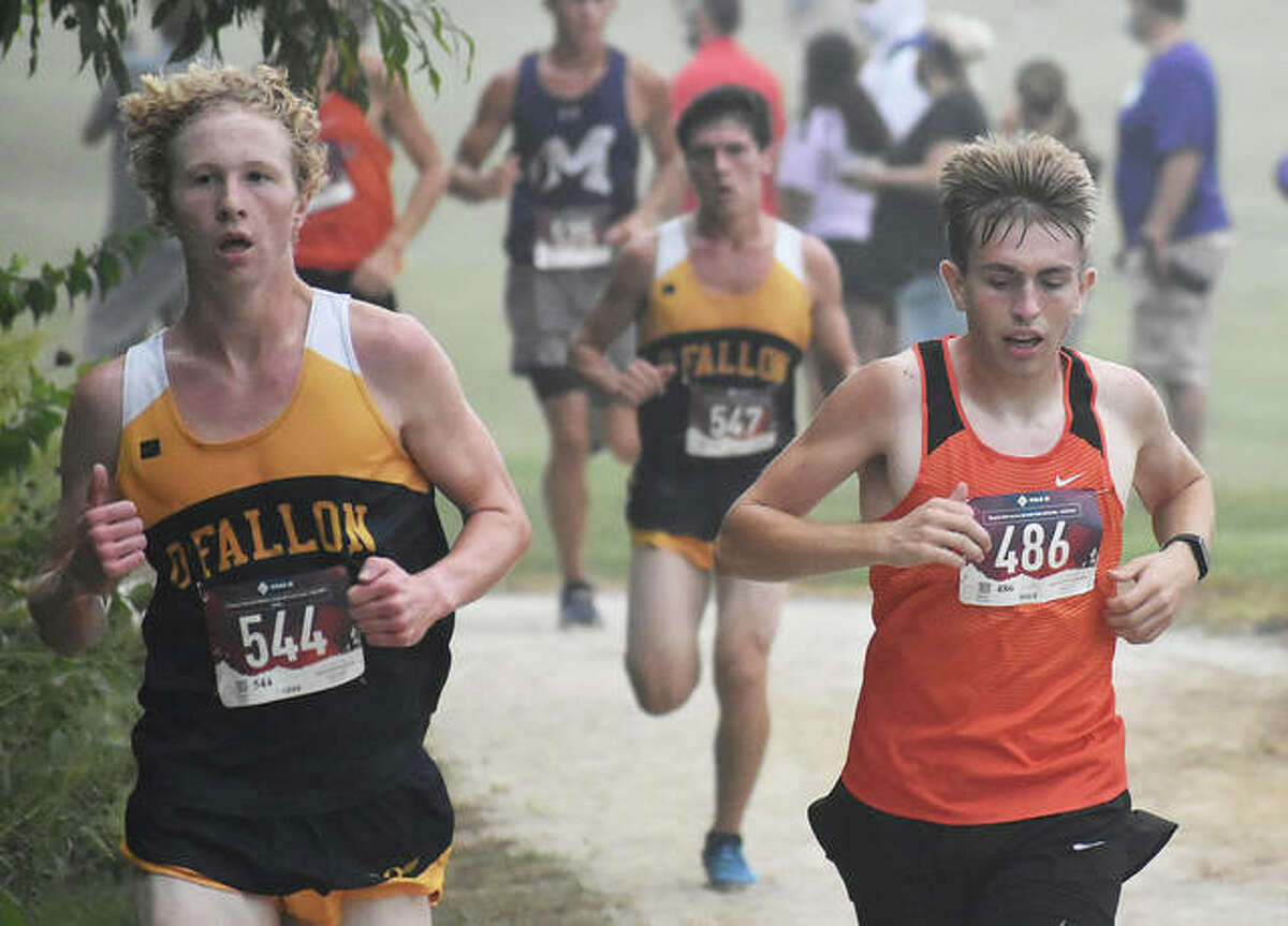 Edwardsville junior Jacob Grandone, right, runs with O'Fallon's Peyton Mueller shortly after the start of the Belleville West Invitational on Saturday in Belleville.