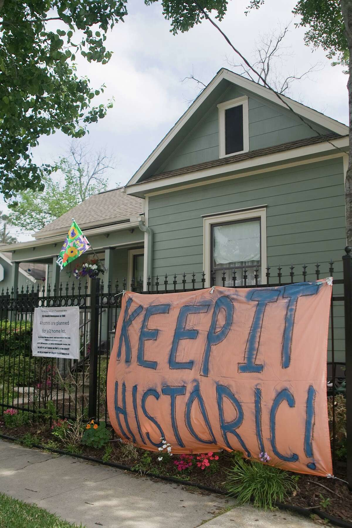 Signs protesting the proposed construction of 4 homes on a double-sized lot at 15th and Rutledge in the Heights Historic District are attached to walls, fences, and stands around the area. Photo by R. Clayton McKee