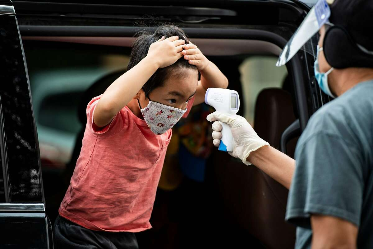 A student has his temperature taken as he arrives at STAR Eco Station Tutoring & Enrichment Center on Sept. 10 in Culver City (Los Angeles County).