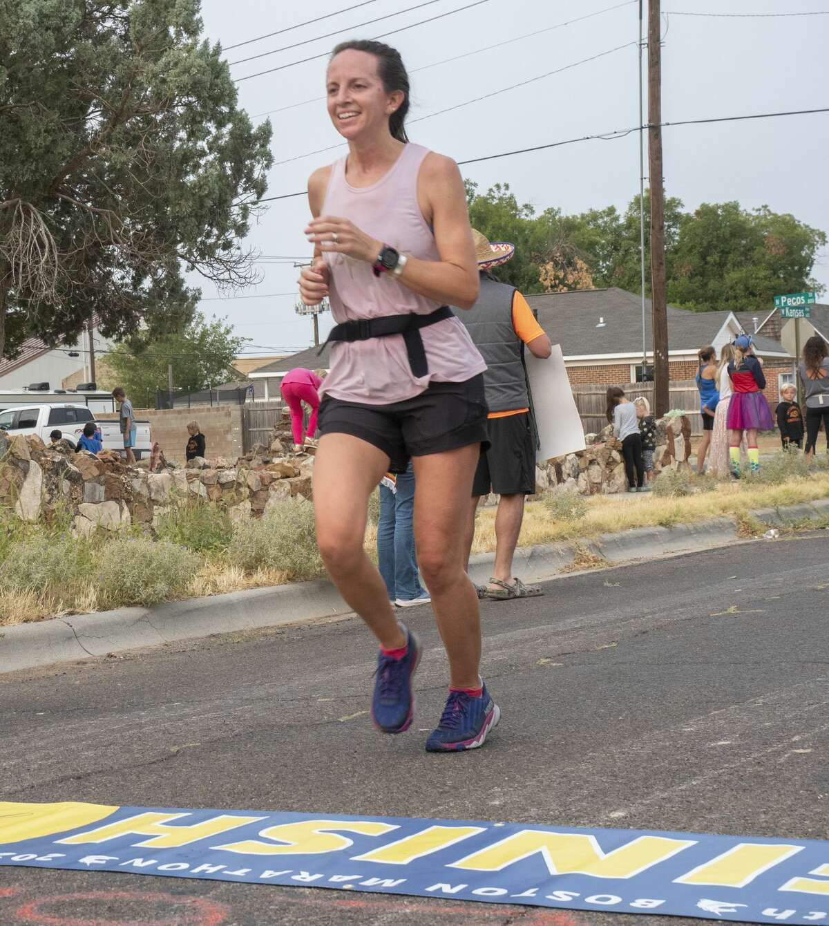 """Katherine Thornton is cheered on as she crosses the finish line as she completes the """"Boston Marathon"""" 09/12/2020 at the corner of Kansas and Pecos Street after running 26.2 miles on a course around Midland. Tim Fischer/Reporter-Telegram"""