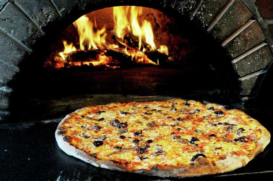 The puttanesca pizza ($8.95) ? which includes olives, anchovies, capers, fresh sauce, red onions and mozzarella ? is an excellent reason to go to Sabina's Wood Fired Restaurant. (Luanne M. Ferris / Times Union) Photo: Luanne M. Ferris