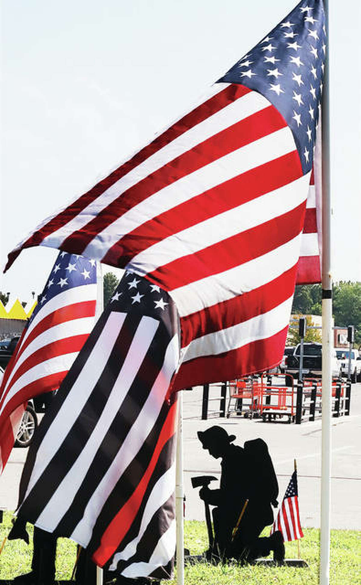 A display of flags and silhouettes is setup at the edge of the parking lot at the Alton Home Depot to honor those who died in the terrorist attacks on the United States 19 years ago Friday. Of the 2,977 people who died in the three attacks, 343 were firefighters.