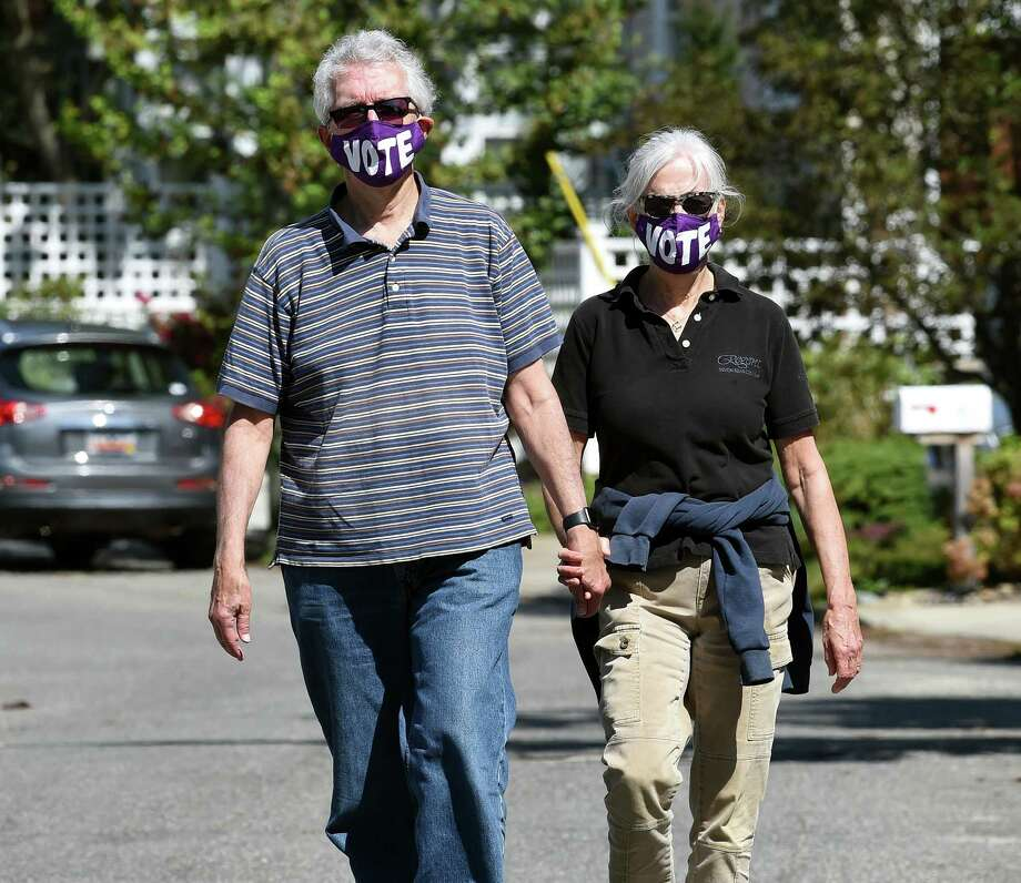 Don Schopiek (left) and his wife, Laurie, take a weekend walk in the Fort Trumbull Beach area of Milford wearing their VOTE face masks on September 12, 2020. Photo: Arnold Gold, Hearst Connecticut Media / New Haven Register