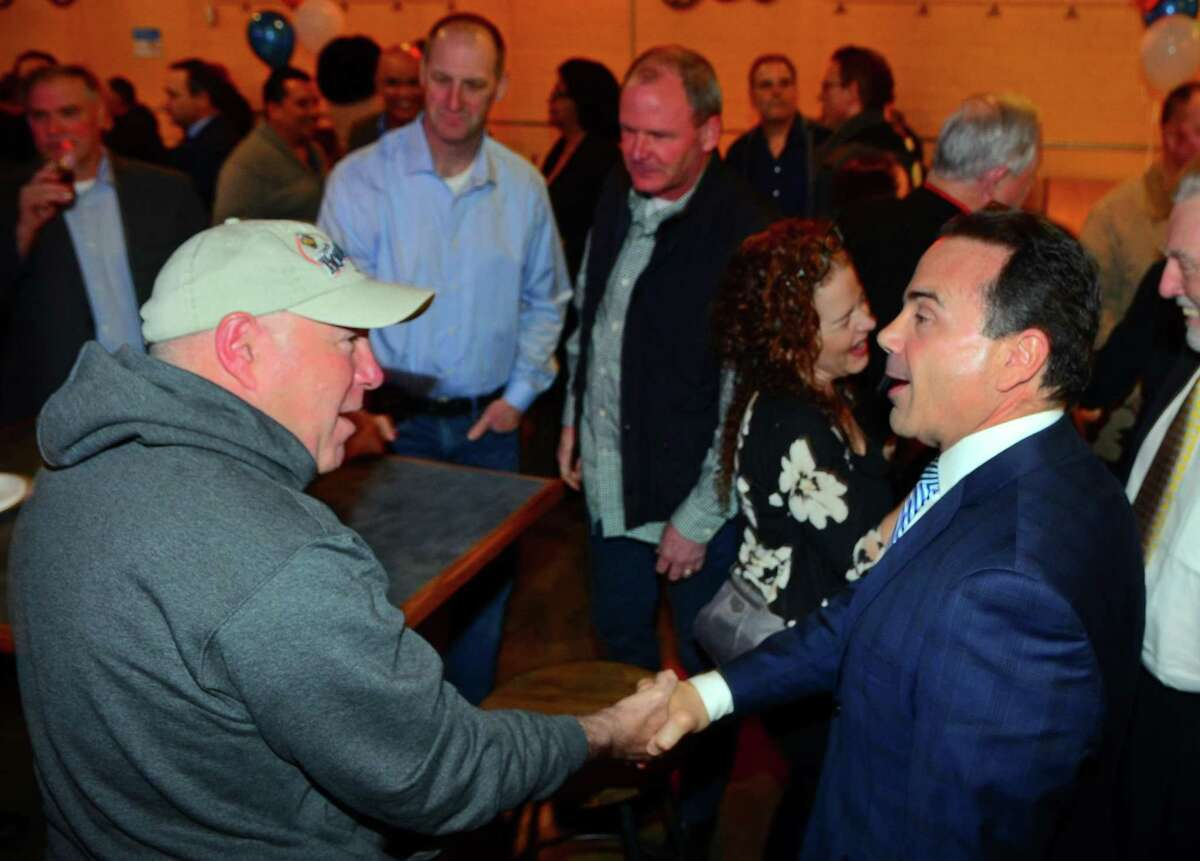 Mayor Joe Ganim, right, greets Bridgeport Police Chief AJ Perez during a fundraiser for Ganim's mayoral campaign at Brewport restaurant in Bridgeport, Conn., on Tuesday April 9, 2019. This is the first fundraiser Ganim has held since last raising money in 2017.