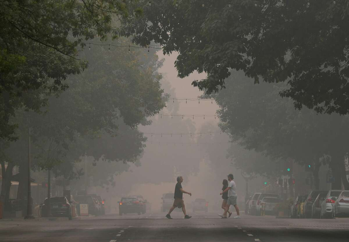 Pedestrians cross Broadway Street as smoke and ash from the nearby North Complex fire drifted through downtown Chico, Calif., on Saturday, September 12, 2020.