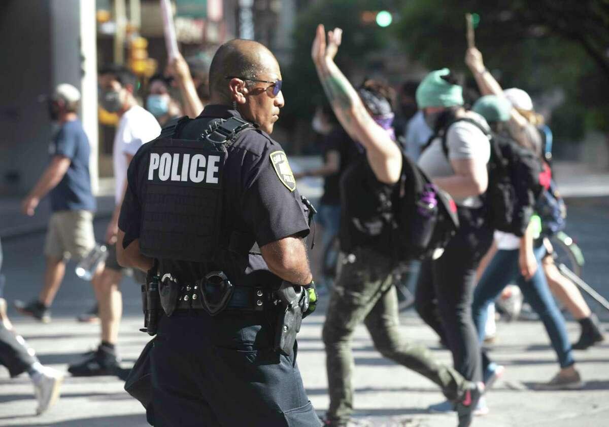 Protestors march downtown past a San Antonio Police officer to San Antonio Travis Park, on Wednesday, June, 3, 2020.