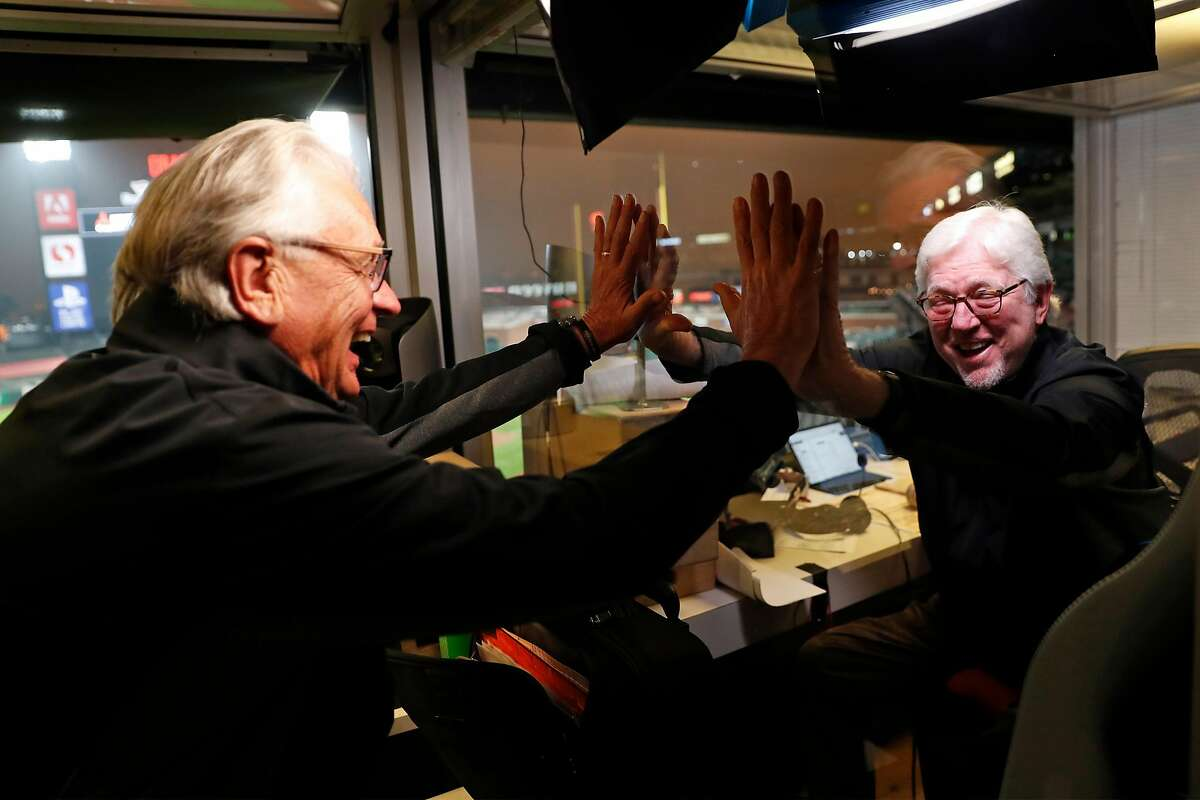 Duane Kuiper (left) and longtime broadcast partner Mike Krukow high-five through Plexiglass before a game at Oracle Park in September.