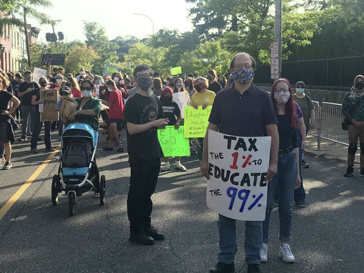 Kevin O'Brien of Schenectady holds a sign outside the governor's mansion in Albany on Saturday at the protest against 20 percent cuts in state education aid to school districts. O'Brien is flanked by his son Kieran, 17, a senior at Schenectady High School to his left and his daughter Shea, 14, a freshman at Schenectady High to his right. Among the organizers of the rally was All of Us. (Photo by Kenneth C. Crowe II/Times Union)