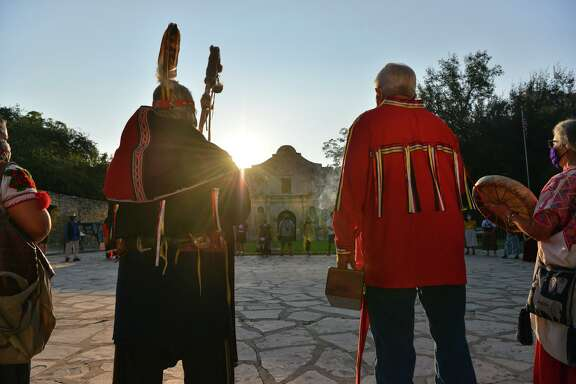 Members of the Tap Pilam Coahuiltecan Nation pause in silence Saturday, Sept. 12, 2020, during this year's sunrise ceremony in front of the Alamo to honor ancestors buried at the Alamo.