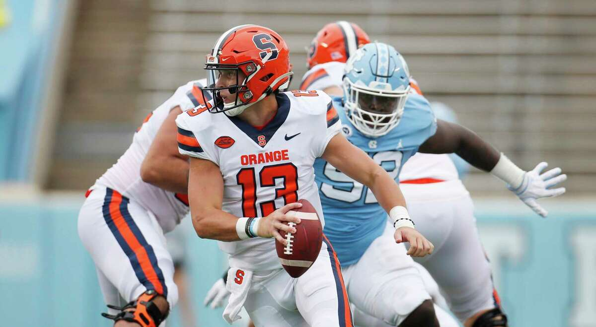 Syracuse quarterback Tommy DeVito (13) scrambles to avoid North Carolina defender Jahlil Taylor (52) in first half of an NCAA college football game, Saturday, Sept. 12, 2020 in Chapel Hill, N.C. (Robert Willett/The News & Observer via AP)