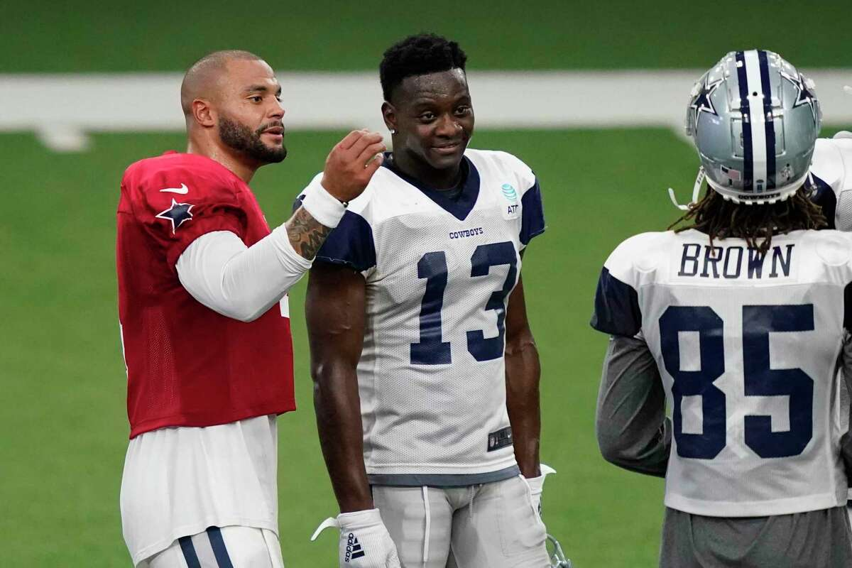 Dallas Cowboys quarterback Dak Prescott (4) talks with wide receivers Michael Gallup (13) and Noah Brown (85) during an NFL training camp practice in Frisco, Texas, Monday, Aug. 31, 2020. (AP Photo/LM Otero)