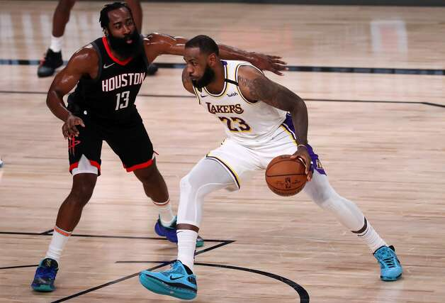 LAKE BUENA VISTA, FLORIDA - SEPTEMBER 12: LeBron James #23 of the Los Angeles Lakers drives the ball against James Harden #13 of the Houston Rockets during the second quarter in Game Five of the Western Conference Second Round during the 2020 NBA Playoffs at AdventHealth Arena at the ESPN Wide World Of Sports Complex on September 12, 2020 in Lake Buena Vista, Florida. NOTE TO USER: User expressly acknowledges and agrees that, by downloading and or using this photograph, User is consenting to the terms and conditions of the Getty Images License Agreement. (Photo by Michael Reaves/Getty Images) Photo: Michael Reaves/Getty Images / 2020 Getty Images