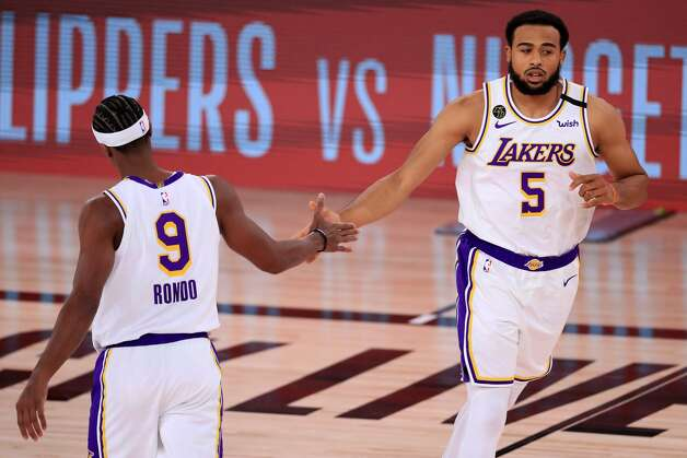 LAKE BUENA VISTA, FLORIDA - SEPTEMBER 12: Rajon Rondo #9 of the Los Angeles Lakers and Talen Horton-Tucker #5 of the Los Angeles Lakers high five during the second quarter against the Houston Rockets in Game Five of the Western Conference Second Round during the 2020 NBA Playoffs at AdventHealth Arena at the ESPN Wide World Of Sports Complex on September 12, 2020 in Lake Buena Vista, Florida. NOTE TO USER: User expressly acknowledges and agrees that, by downloading and or using this photograph, User is consenting to the terms and conditions of the Getty Images License Agreement. (Photo by Michael Reaves/Getty Images) Photo: Michael Reaves/Getty Images / 2020 Getty Images