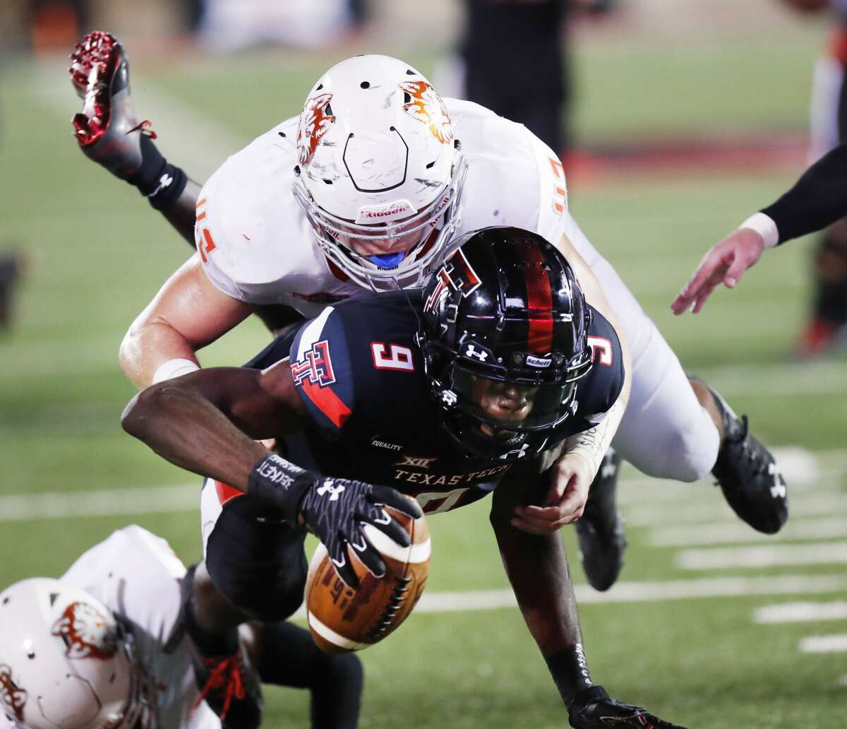 Houston Baptist's Brennan Young, top, tackles Texas Tech's T.J. Vasher (9) on the 1-yard line in the first half of an NCAA college football game, Saturday, Sept. 12, 2020, in Lubbock.