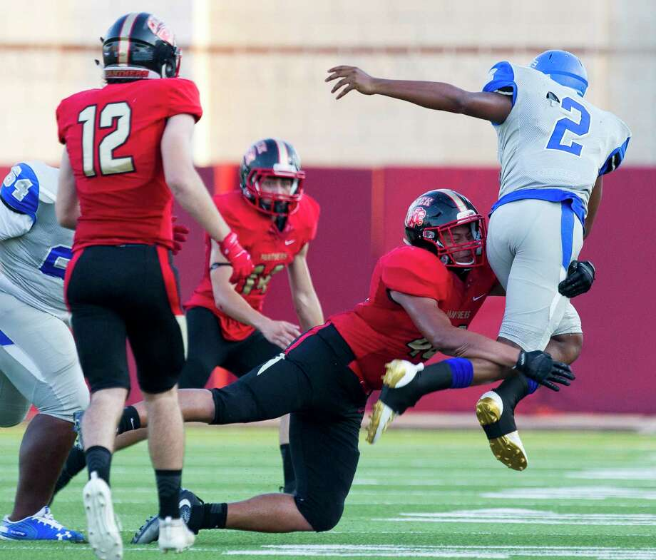 Caney Creek defensive linemen Edgar Heredia (46) tackles Pro-Vision Academy quarterback Trajon Duhart (2) in midair during the first quarter of a non-district high school football game at Woodforest Bank Stadium, Thursday, Sept. 5, 2019, in Shenandoah. Photo: Jason Fochtman, Houston Chronicle / Staff Photographer / Houston Chronicle