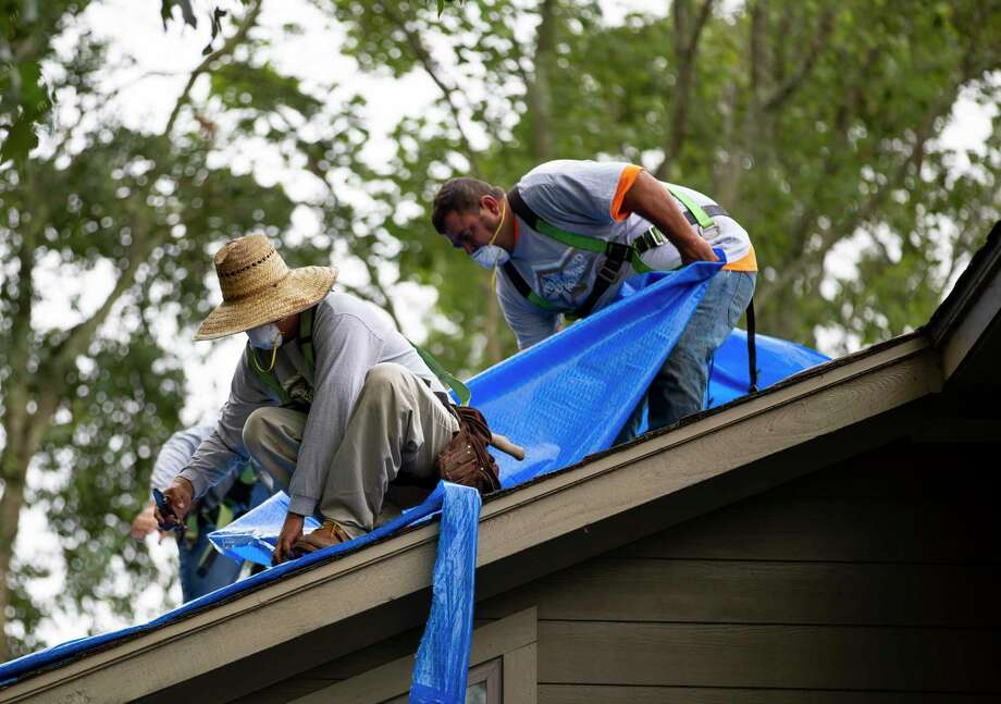 Roofing tradesmen from Texas Engineered Roofing and General Contracting remove a protective roofing tarp on a home near Lake Conroe, Friday, Sept. 11, 2020. The company lead a not-for-profit community relations project in the Walden community after they heard of a community member receiving a botched job from a previous contractor. Photo: Gustavo Huerta, Houston Chronicle / Staff Photographer / 2020 © Houston Chronicle