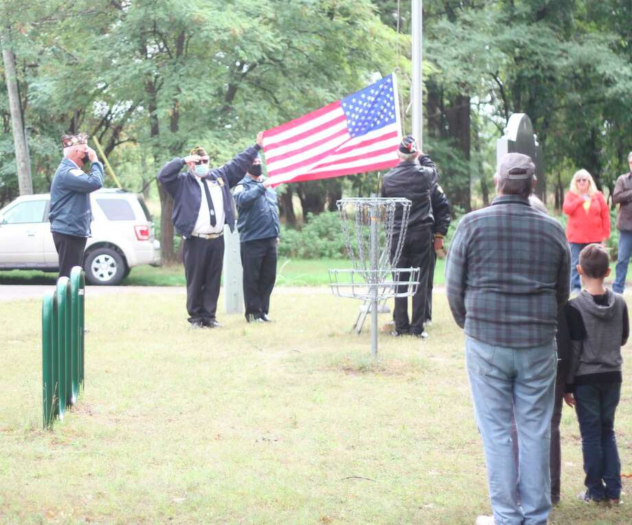 "Manistee Veterans of Foreign Wars Post No. 4499 performs a flag raising ceremony to open Bring Disc Golf to Manistee's ""A Day a the Park"" event Saturday. (Kyle Kotecki/News Advocate)"