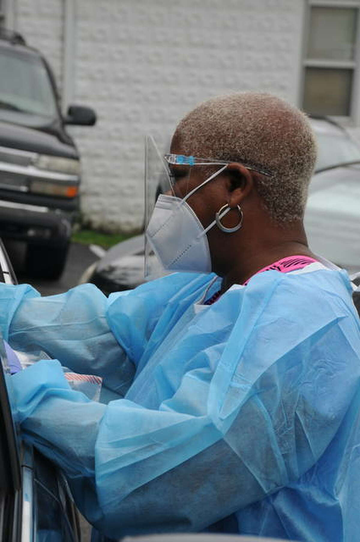 Pamela Palacios reaches inside of a car to perform a COVID-19 test on Saturday.