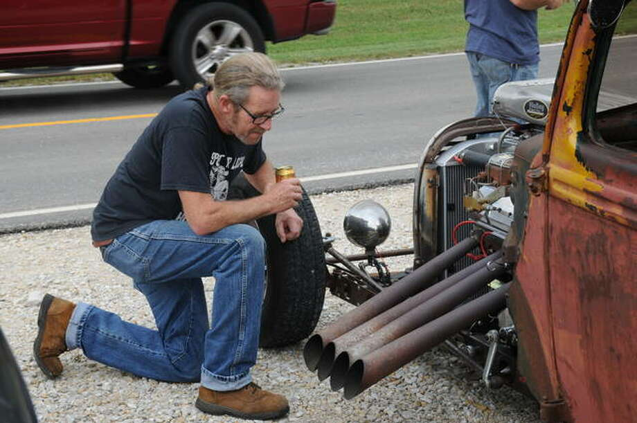 A spectator admires the engine of a cobbled-together car at Saturday's Rat Rod Show in Grafton. The one-of-a-kind vehicles often are spare-parts creations their owners have welded and cobbled-together to create unique machines.