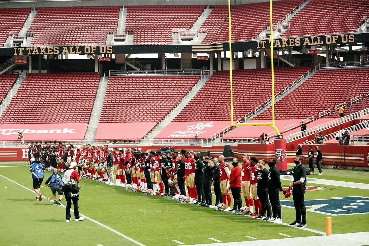 """San Francisco 49ers' players, coaches and staff stand in end zone as """"Lift Up Every Voice"""" plays before Niners play Arizona Cardinals during NFL game at Levi's Stadium in Santa Clara, Calif., on Sunday, September 13, 2020."""