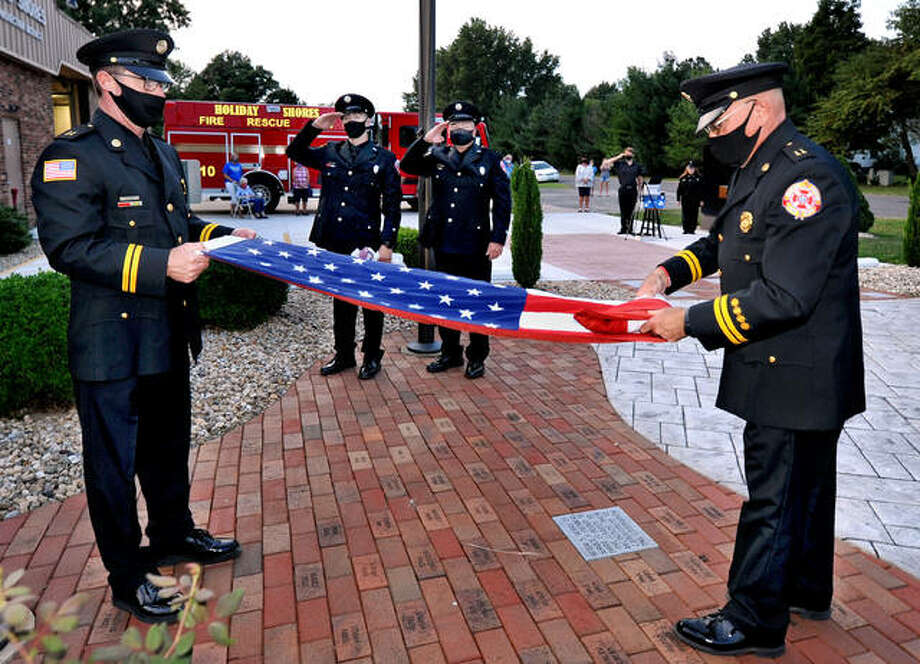 Holiday Shores Fire Protection District's Capt. Darl Opel, left front, and Tim Dyer, right front, retire the colors during a ceremony Friday at the firehouse to memorialize firefighters who lost their lives responding to the attack in New York City on Sept. 11, 2001. Photo: Thomas Turney | For The Intelligencer