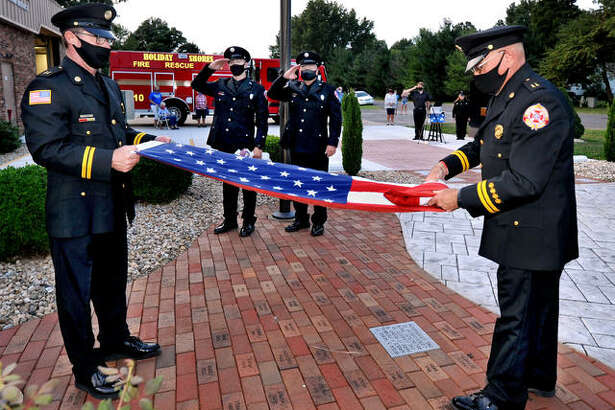 Holiday Shores Fire Protection District's Capt. Darl Opel, left front, and Tim Dyer, right front, retire the colors during a ceremony Friday at the firehouse to memorialize firefighters who lost their lives responding to the attack in New York City on Sept. 11, 2001.