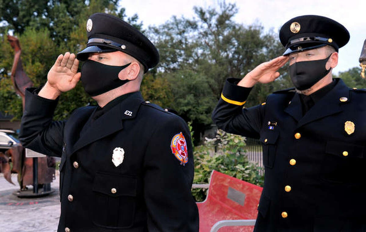 Engineer Bobby French, left, and Lt. Todd Frank hold a salute during a Sept. 11 ceremony at the Holiday Shores Fire Protection District Friday. A garden at the Holiday Shores firehouse, background, features a twisted steel beam from the World Trade Center.