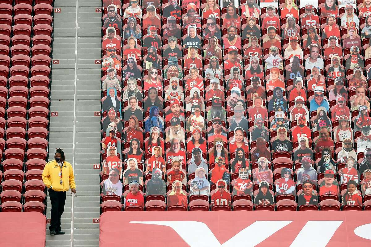 An usher at Levi's Stadium stands next to an end-zone section of fan cardboard cutouts. The cardboard fans were a cute idea at first, but it's starting to get creepy.