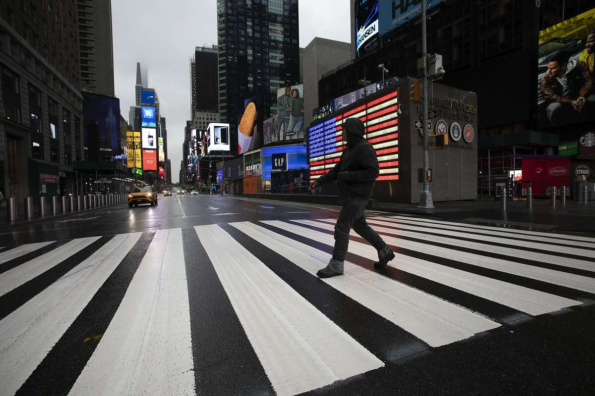 In this March 23, 2020, file photo, a man crosses the street in a nearly empty Times Square, which normally saw around 400,000 pedestrians per day pre-pandemic.