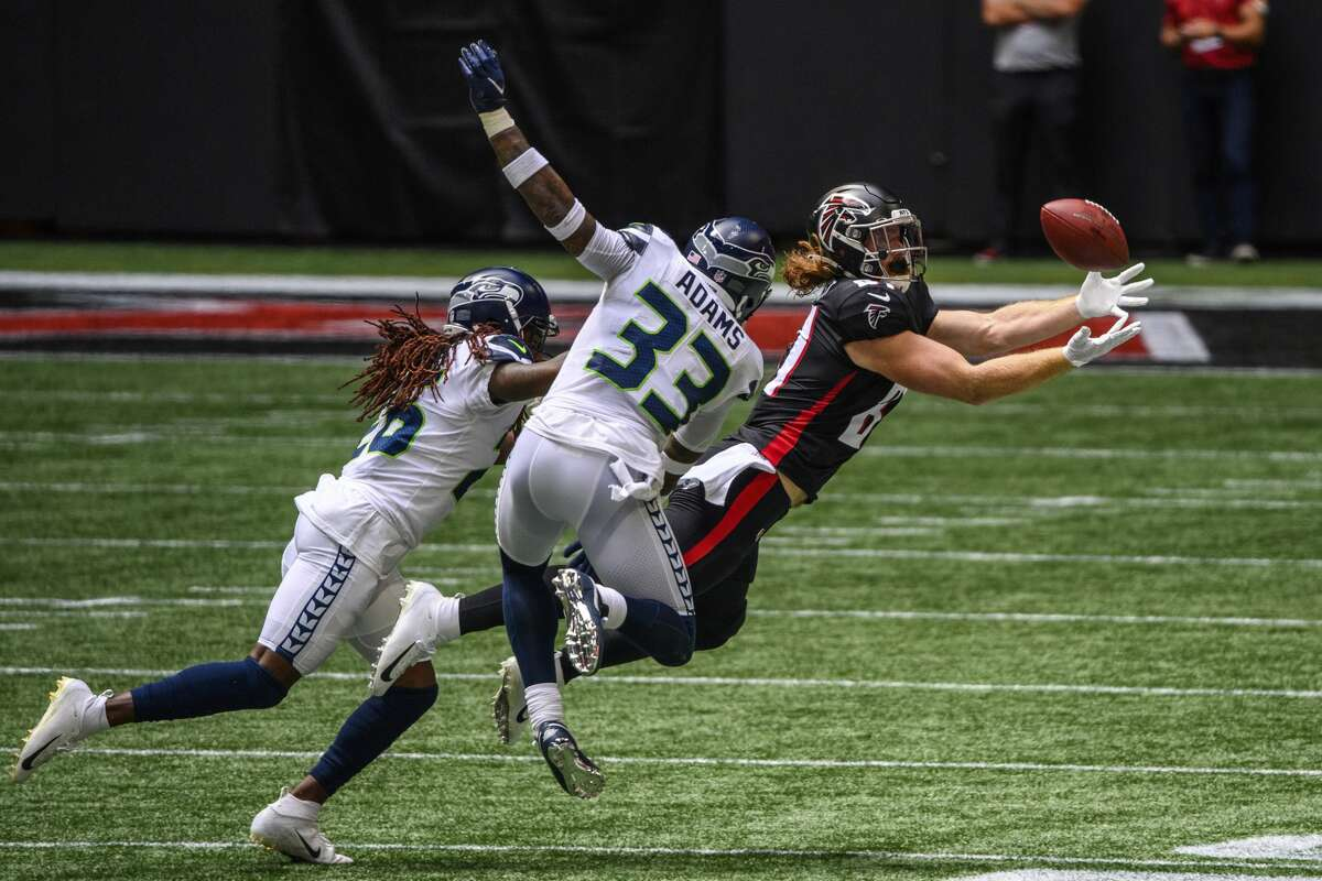 Atlanta Falcons tight end Hayden Hurst (81) catches a pass as Seattle Seahawks strong safety Jamal Adams (33) and cornerback Shaquill Griffin (26) defend during the first half of an NFL football game, Sunday, Sept. 13, 2020, in Atlanta. (AP Photo/Danny Karnik)