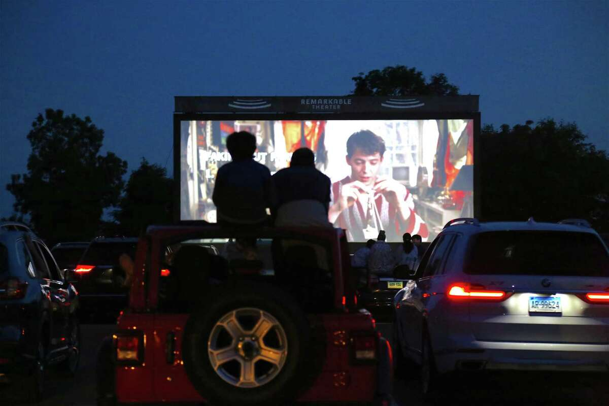 Viewers atop their car at the drive-in premiere of the new Remarkable Theater on June 27, 2020, in Westport, Conn.