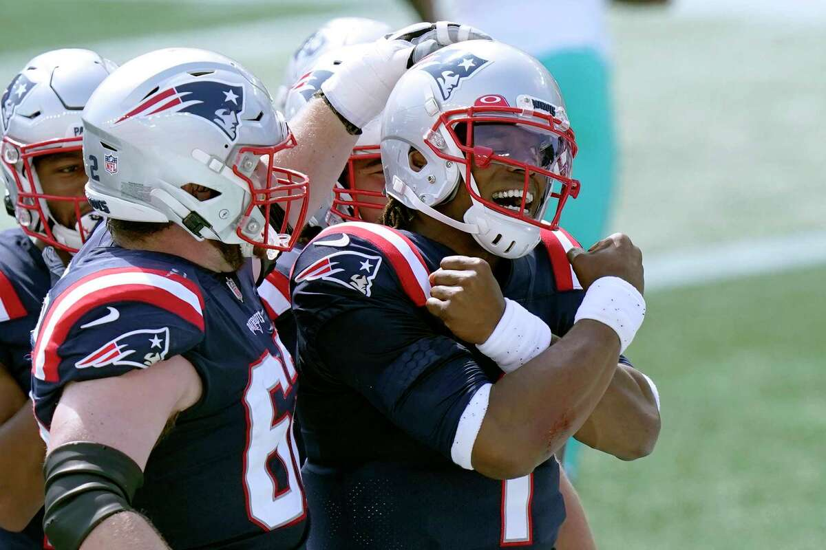 New England Patriots quarterback Cam Newton (1) celebrates his rushing touchdown against the Miami Dolphins with teammates in the first half of an NFL football game, Sunday, Sept. 13, 2020, in Foxborough, Mass. (AP Photo/Steven Senne)