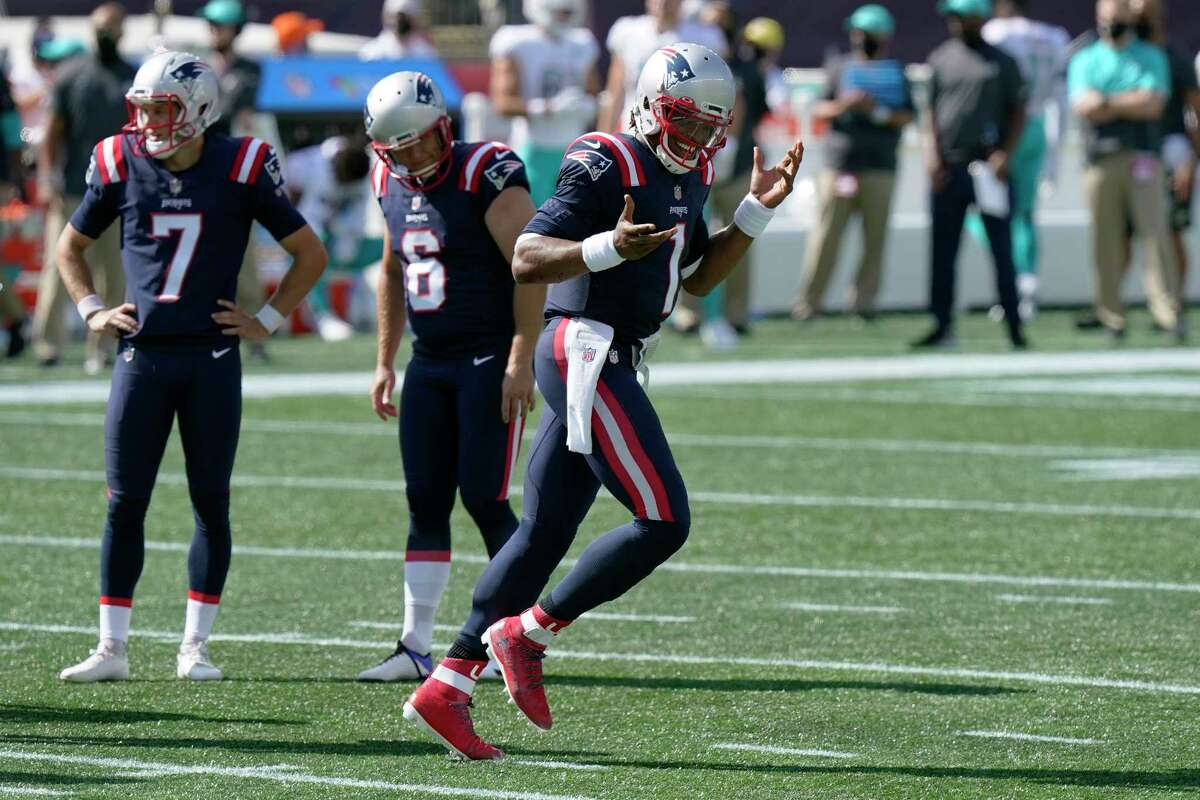 New England Patriots quarterback Cam Newton, right, celebrates his second rushing touchdown as he heads to the bench in the second half of an NFL football game against the Miami Dolphins, Sunday, Sept. 13, 2020, in Foxborough, Mass. (AP Photo/Steven Senne)