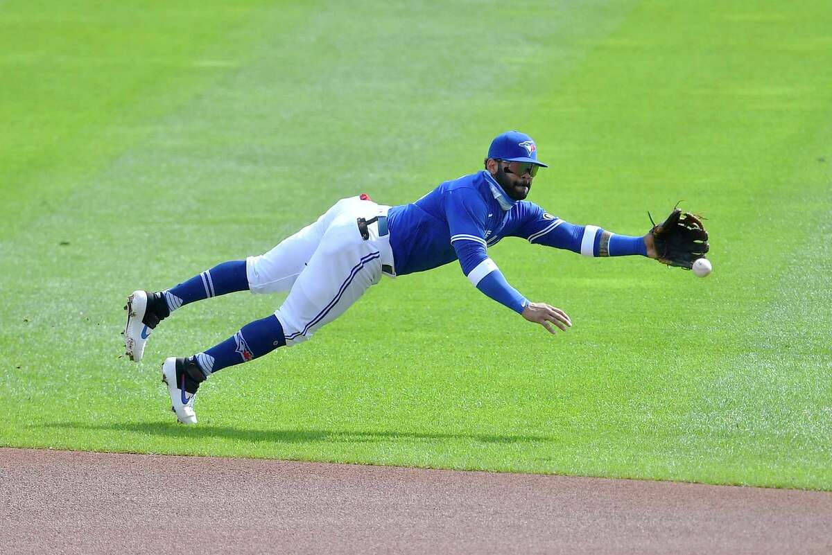 Toronto Blue Jays' second baseman Jonathan Villar dives for a ball hit for a single by New York Mets' Jeff McNeil during the first inning of a baseball game in Buffalo, N.Y., Sunday, Sept. 13, 2020. (AP Photo/Adrian Kraus)