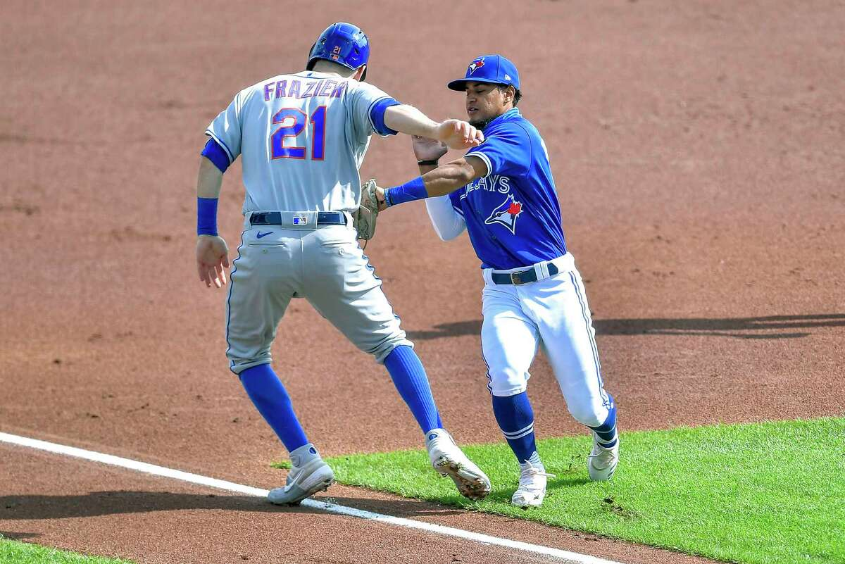 Toronto Blue Jays shortstop Santiago Espinal, right, tags New York Mets' Todd Frazier for an out on a rundown during the first inning of a baseball game in Buffalo, N.Y., Sunday, Sept. 13, 2020. (AP Photo/Adrian Kraus)