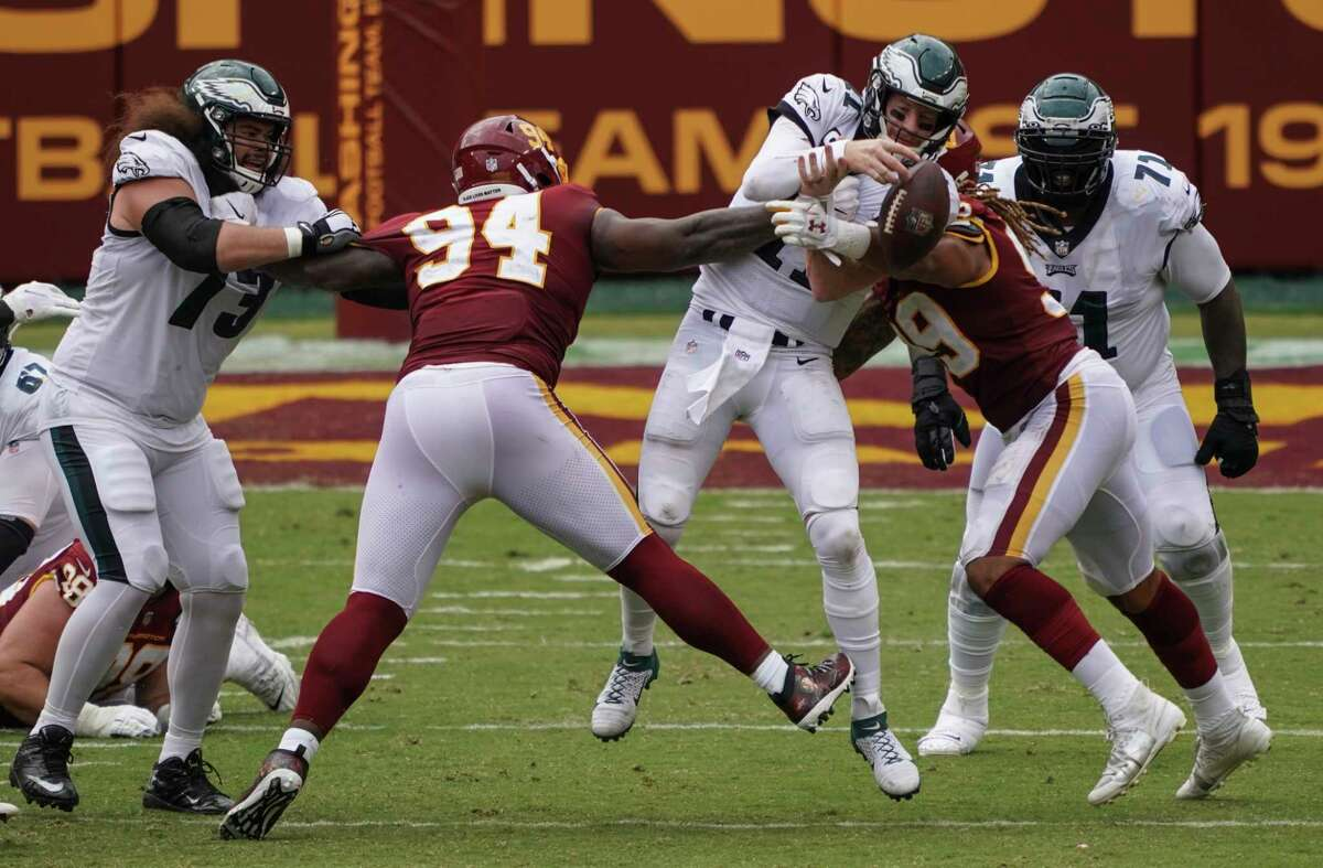 Philadelphia Eagles quarterback Carson Wentz gets sacked by Washington Football Team tackle Daron Payne, left, and defensive end Chase Young in the fourth quarter at FedEx Field in Landover, Md., on Sunday, Sept. 13, 2020. MUST CREDIT: Washington Post photo by Toni L. Sandys