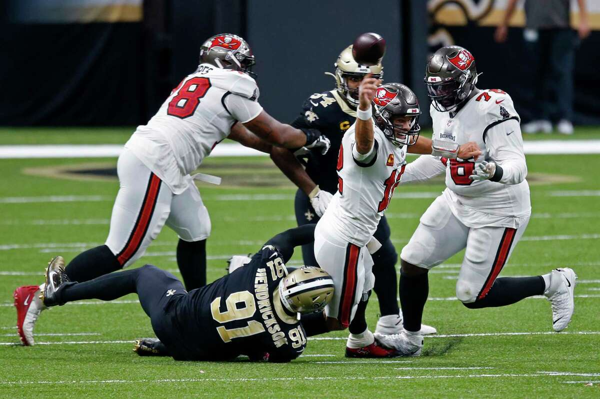 Tampa Bay Buccaneers quarterback Tom Brady (12) tries to throw as he is brought down by New Orleans Saints defensive end Trey Hendrickson (91) in the first half of an NFL football game in New Orleans, Sunday, Sept. 13, 2020. He was called for intentional grounding on the play. (AP Photo/Butch Dill)
