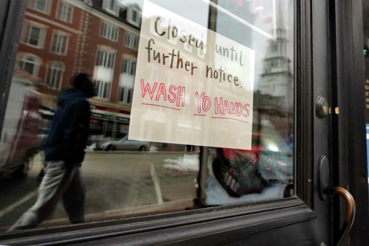 FILE - In this March 25, 2020, file photo, a closed sign hangs in the window of a shop in Portsmouth, N.H. Most of the restaurant and retail businesses in the city have closed, with some offering takeout or pick-up orders, due to the virus outbreak. (AP Photo/Charles Krupa, File)