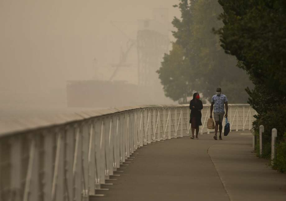 """SEATTLE, WA - SEPTEMBER 12: People walk near the waterfront as smoke from wildfires fills the air on September 12, 2020 in Seattle, Washington. According to the National Weather Service, the air quality in Seattle remained at """"unhealthy"""" levels Saturday after a large smoke cloud from wildfires on the West Coast settled over the area. (Photo by Lindsey Wasson/Getty Images) Photo: Lindsey Wasson/Getty Images / 2020 Getty Images"""