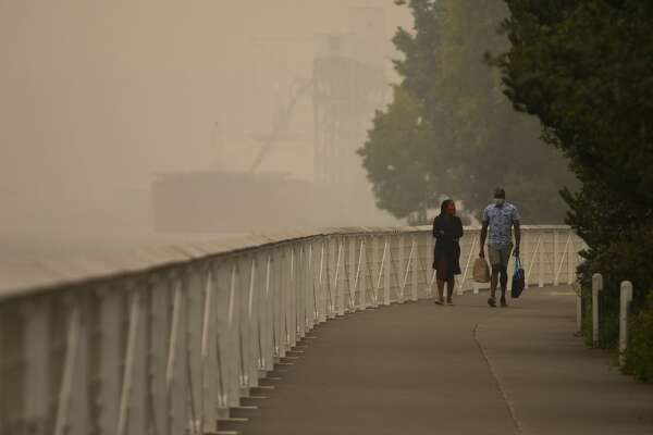 """SEATTLE, WA - SEPTEMBER 12: People walk near the waterfront as smoke from wildfires fills the air on September 12, 2020 in Seattle, Washington. According to the National Weather Service, the air quality in Seattle remained at """"unhealthy"""" levels Saturday after a large smoke cloud from wildfires on the West Coast settled over the area. (Photo by Lindsey Wasson/Getty Images)"""