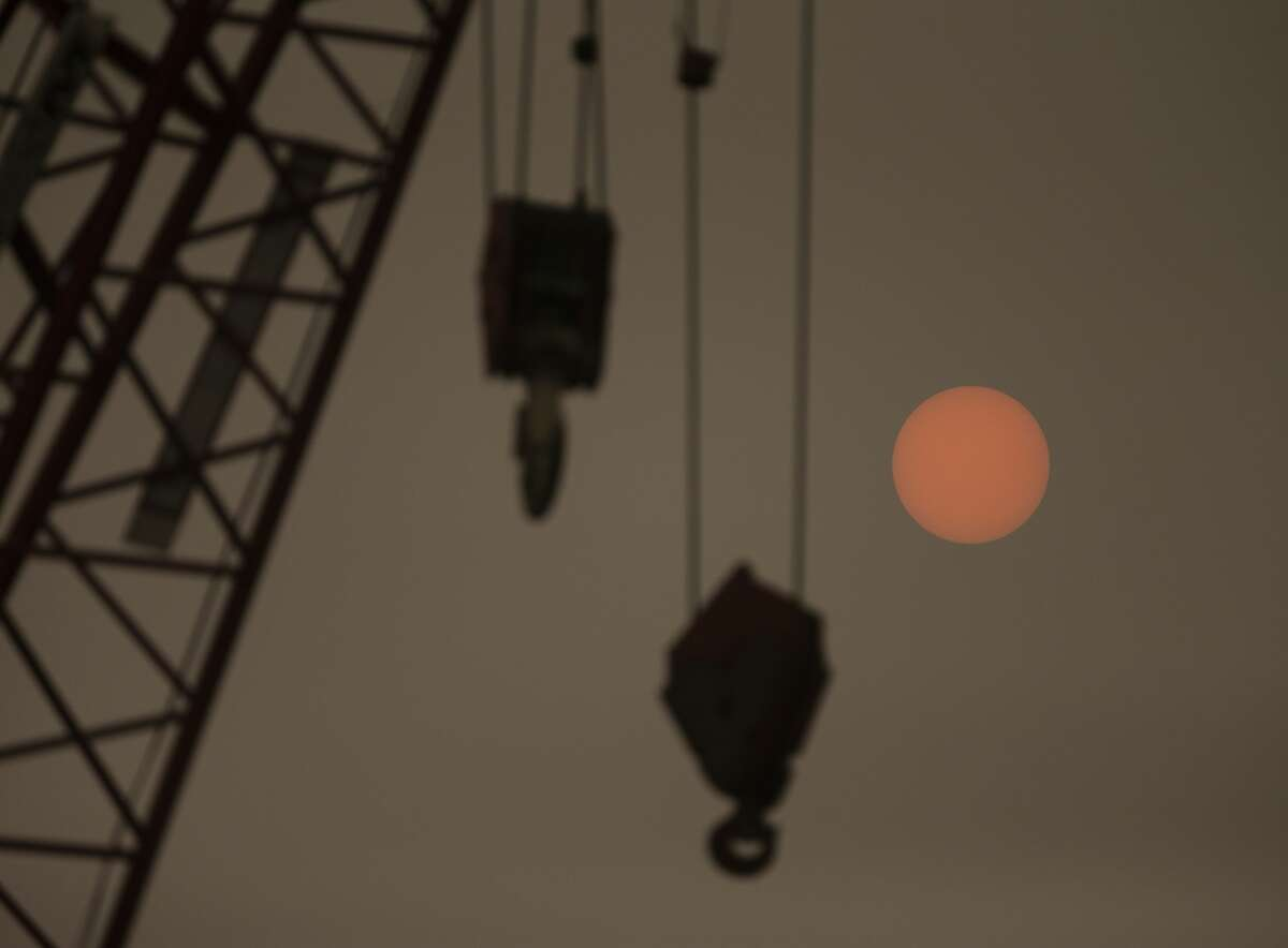 A construction crane on the waterfront is silhouetted as the sun glows through wildfire smoke on September 12, 2020 in Seattle, Washington.