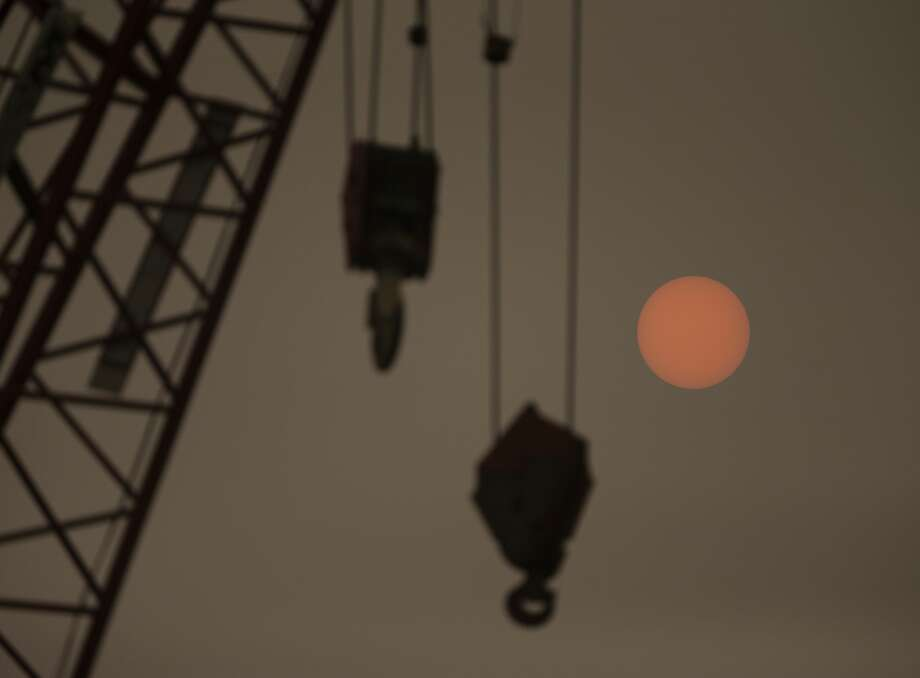 """SEATTLE, WA - SEPTEMBER 12: A construction crane on the waterfront is silhouetted as the sun glows through wildfire smoke on September 12, 2020 in Seattle, Washington. According to the National Weather Service, the air quality in Seattle remained at """"unhealthy"""" levels Saturday after a large smoke cloud from wildfires on the West Coast settled over the area. (Photo by Lindsey Wasson/Getty Images) Photo: Lindsey Wasson/Getty Images / 2020 Getty Images"""