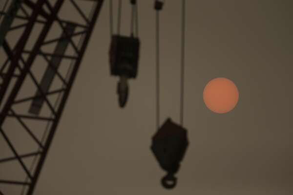 """SEATTLE, WA - SEPTEMBER 12: A construction crane on the waterfront is silhouetted as the sun glows through wildfire smoke on September 12, 2020 in Seattle, Washington. According to the National Weather Service, the air quality in Seattle remained at """"unhealthy"""" levels Saturday after a large smoke cloud from wildfires on the West Coast settled over the area. (Photo by Lindsey Wasson/Getty Images)"""
