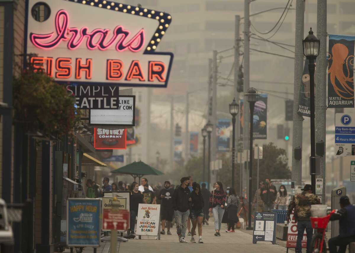 SEATTLE, WA - SEPTEMBER 12: People walk near Ivar's Fish Bar on the waterfront as smoke from wildfires fills the air on September 12, 2020 in Seattle, Washington. According to the National Weather Service, the air quality in Seattle remained at