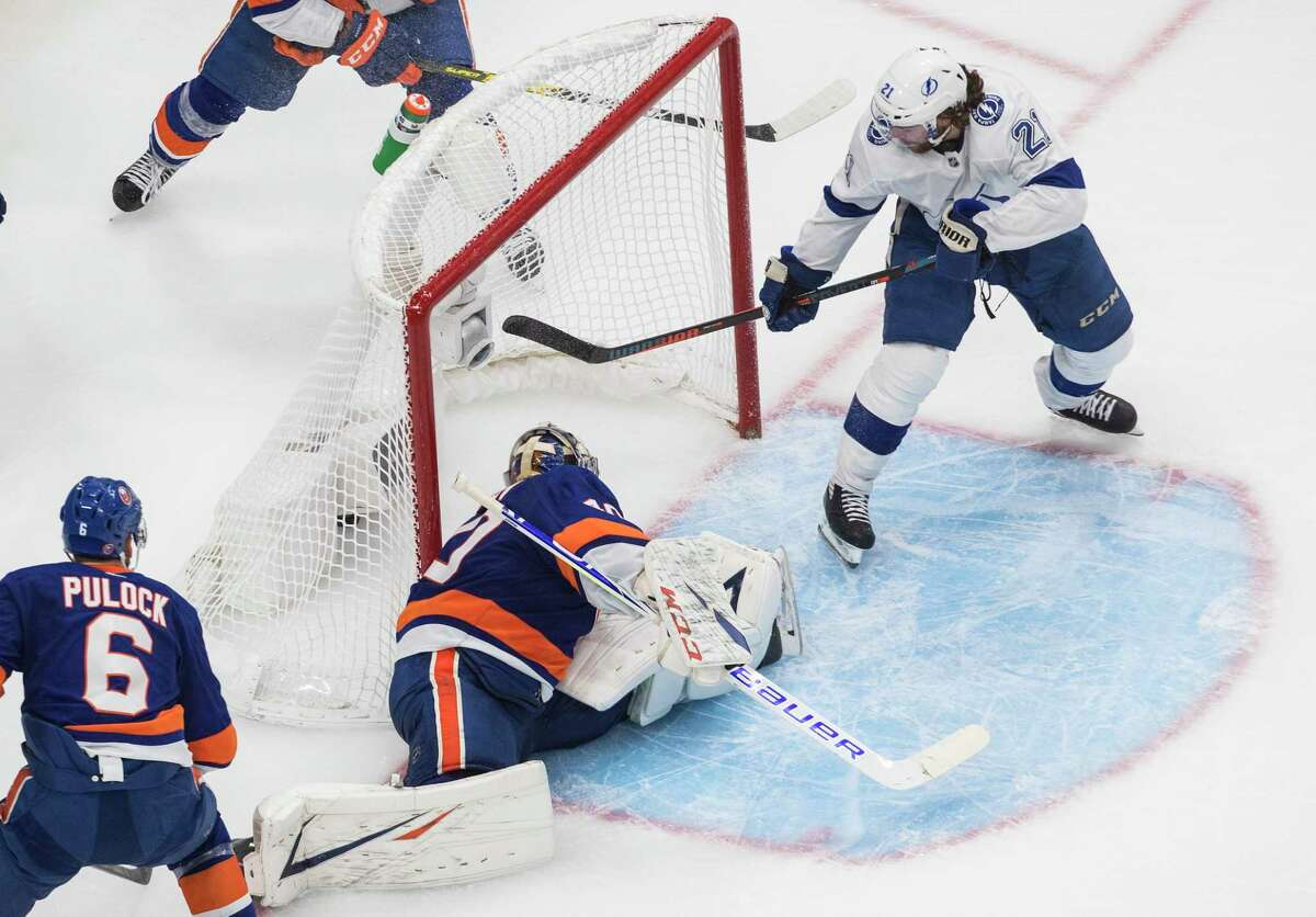 Tampa Bay Lightning's Brayden Point (21) scores a goal on New York Islanders goalie Semyon Varlamov (40) during the third period of an NHL Eastern Conference final playoff game in Edmonton, Alberta, on Sunday, Sept. 13, 2020. (Jason Franson/The Canadian Press via AP)